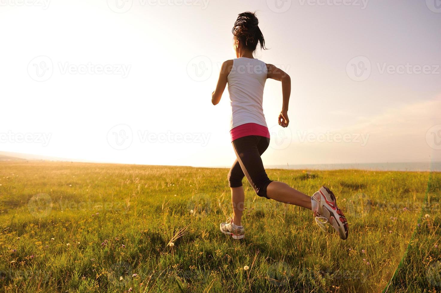 atleta corridore in esecuzione sul campo di erba alba / tramonto foto