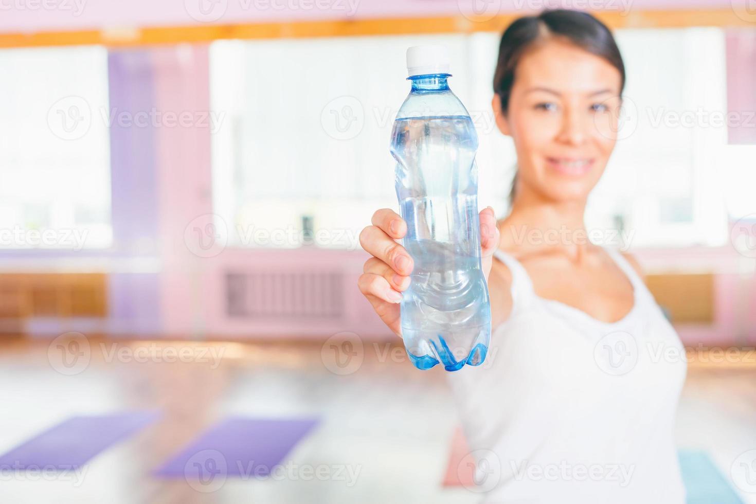 donna asiatica felice dopo l'esercizio di forma fisica che tiene acqua naturale foto
