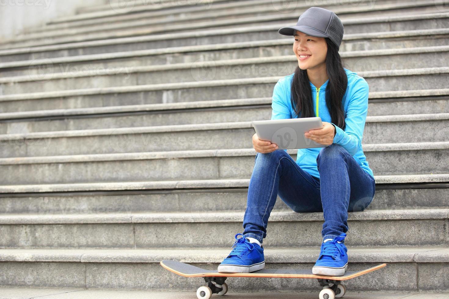 lo skateboarder della giovane donna usa la sua compressa digitale sedersi sulle scale foto