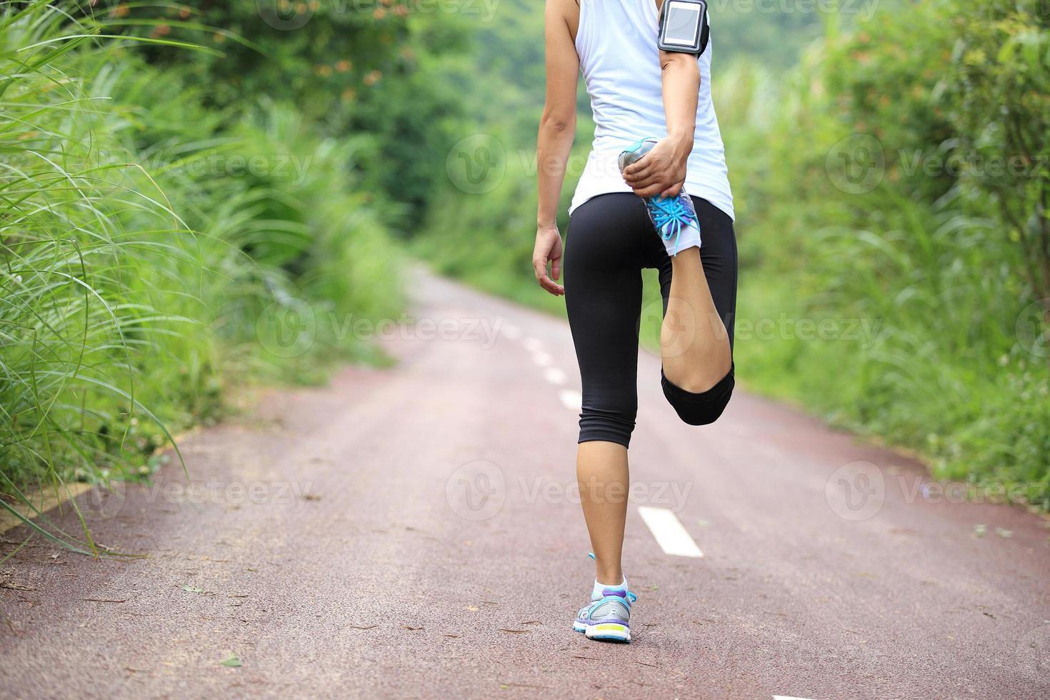 atleta corridore che allunga le gambe foto