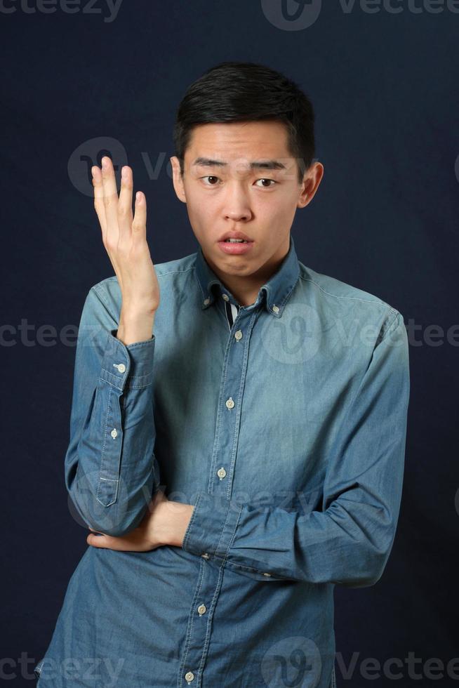 giovane uomo asiatico dispiaciuto che gesturing con una mano foto