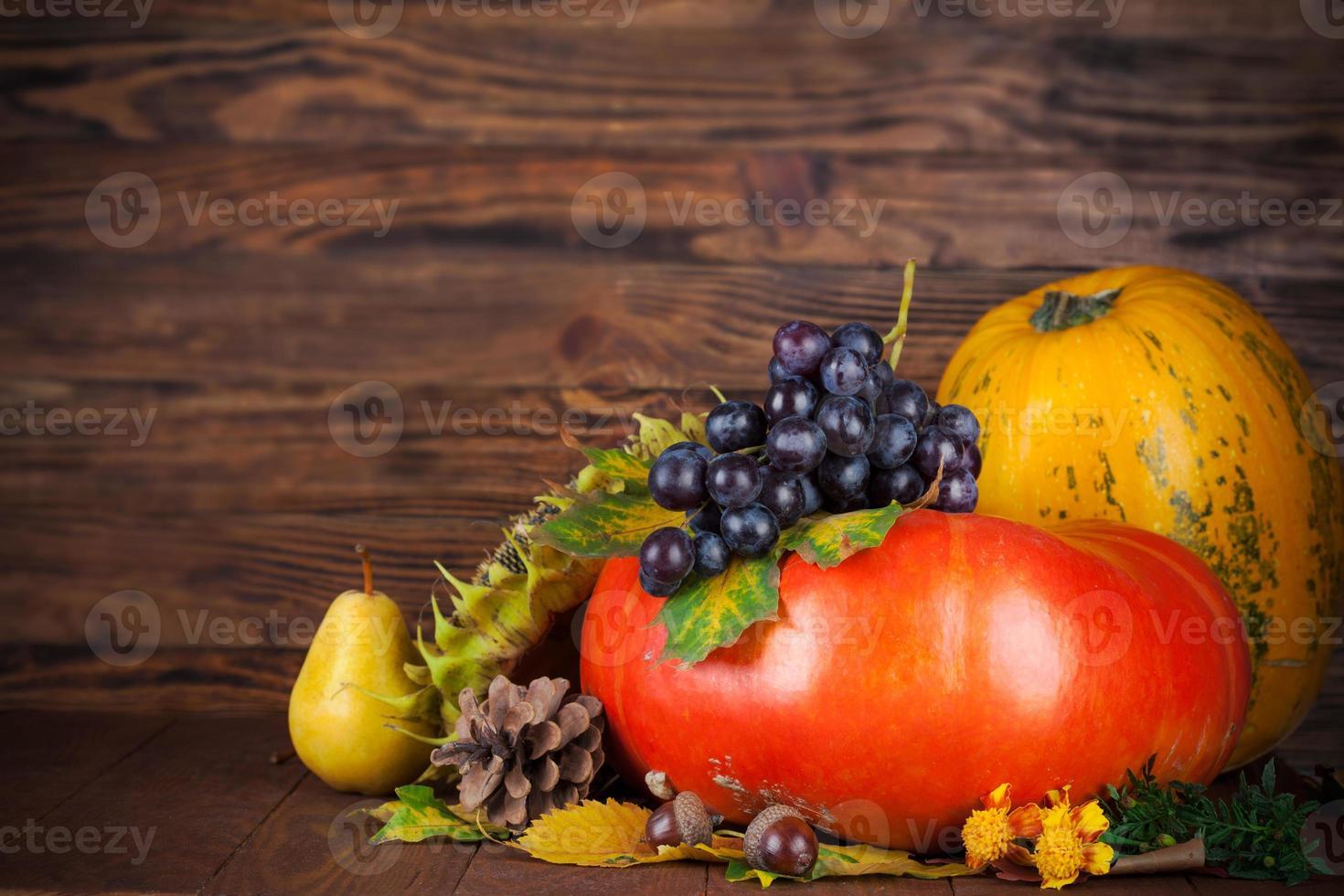 natura morta autunnale con zucca e uva su tavola di legno foto
