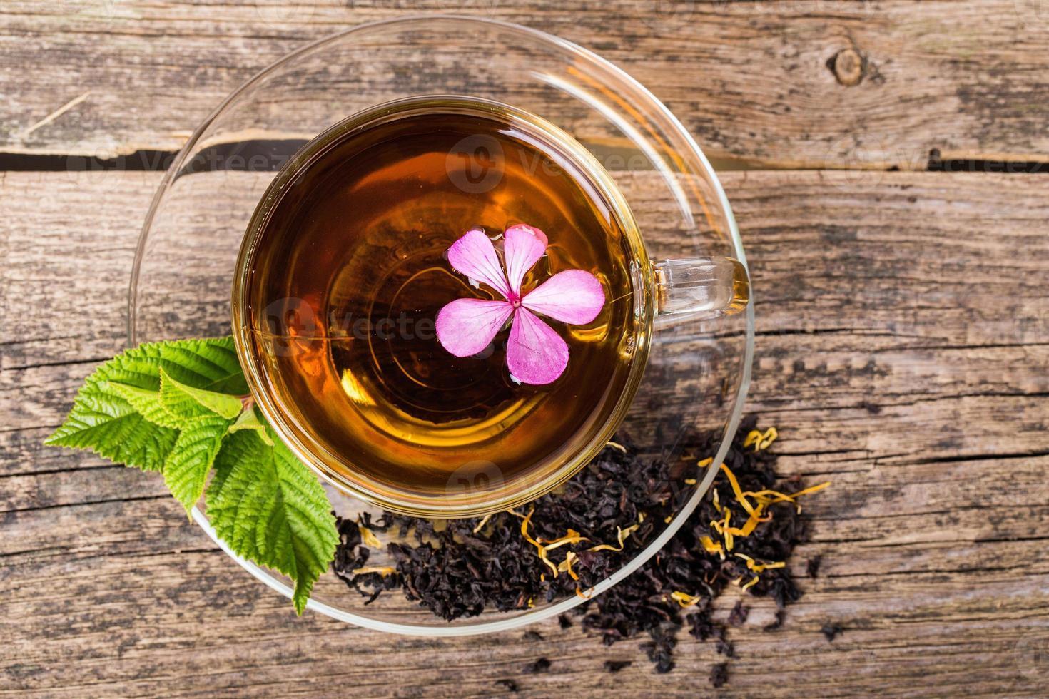 tè con fiore rosa e foglia di menta, su legno foto