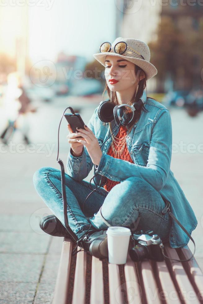 ragazza dei pantaloni a vita bassa nella musica d'ascolto di cappello e occhiali foto