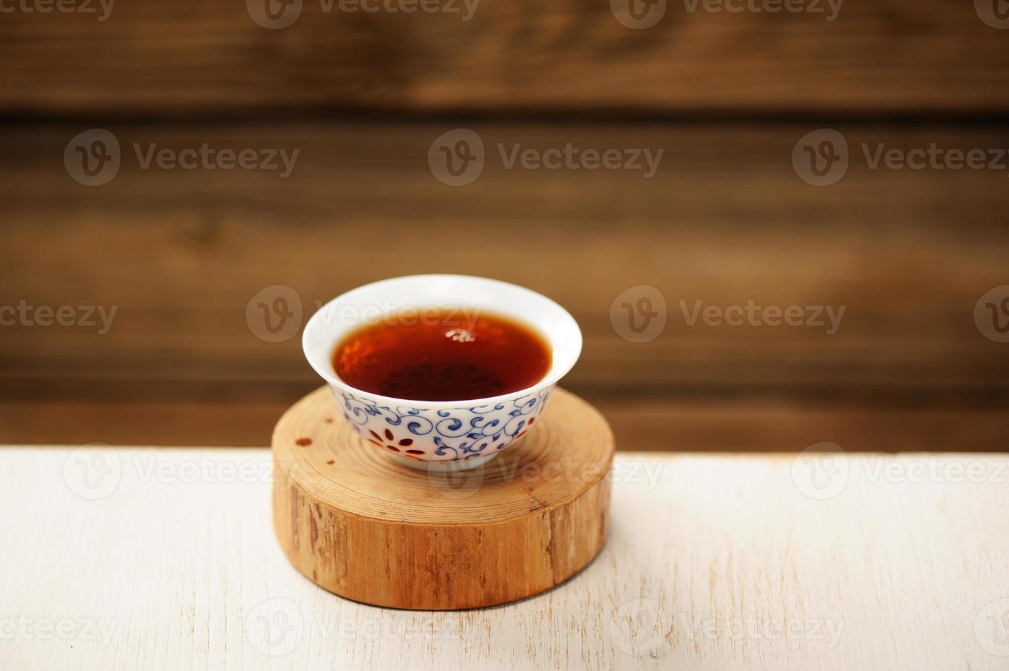 tè nero puerh in una ciotola bianca su supporto in legno foto