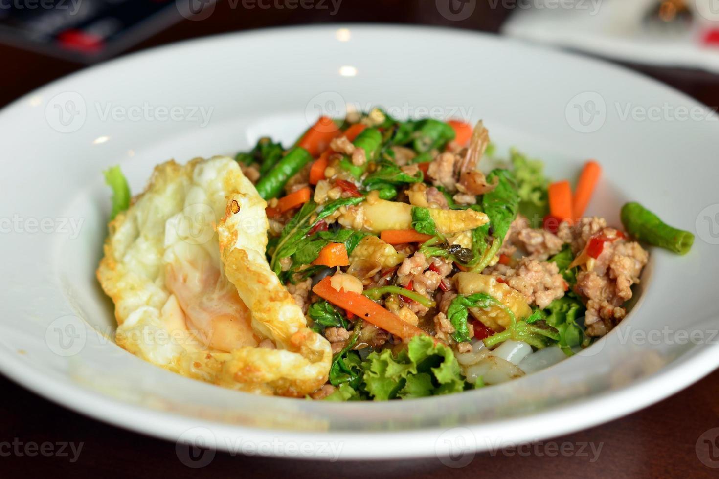 basilico fritto mescolare la tagliatella tailandese con carne di maiale tritata con l'uovo fritto foto