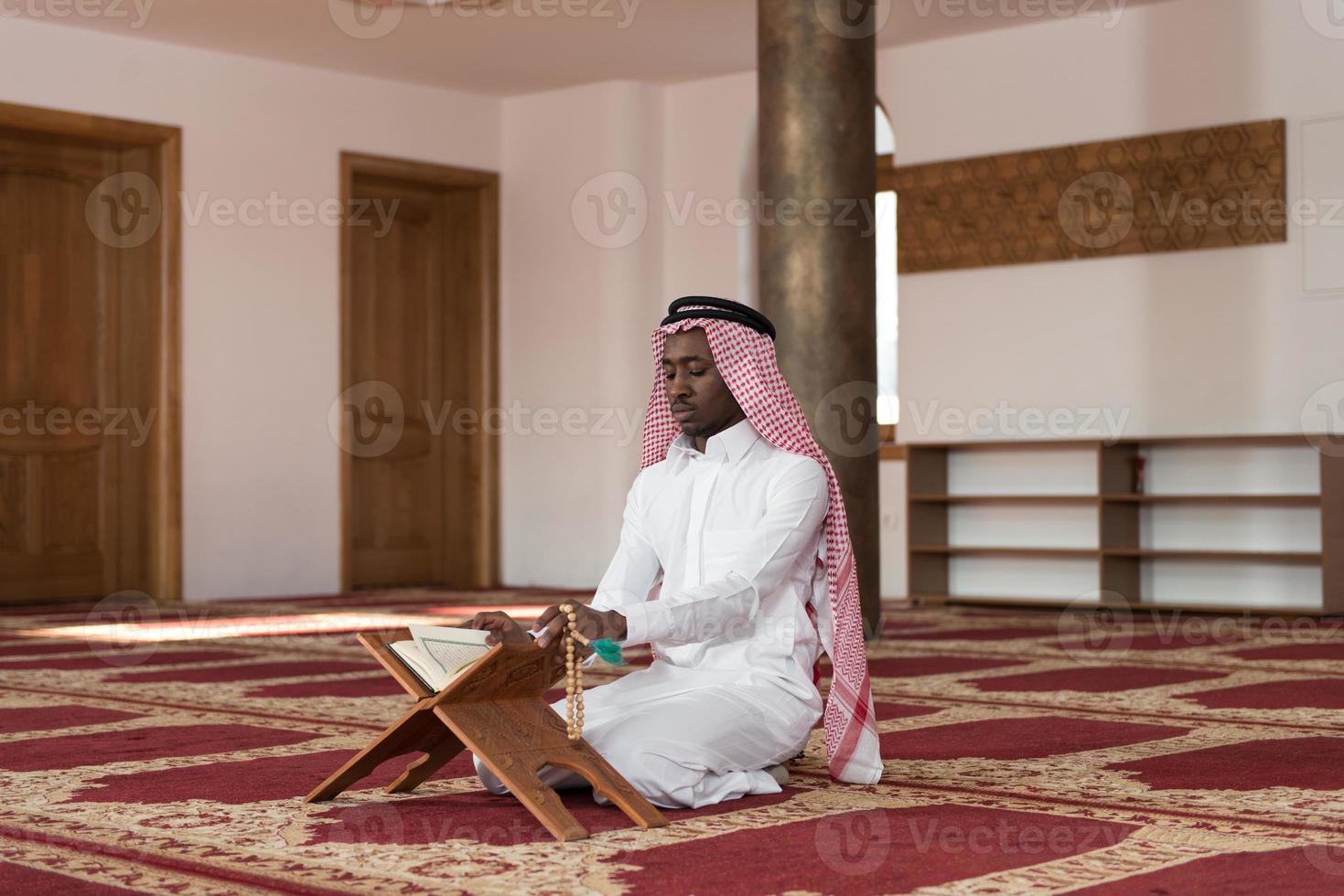 uomo d'affari nero che legge il Corano foto
