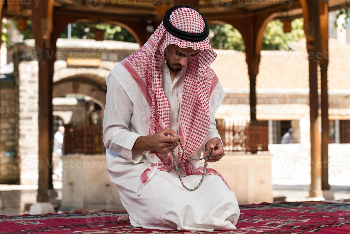 primo piano delle mani maschili che pregano con il rosario foto