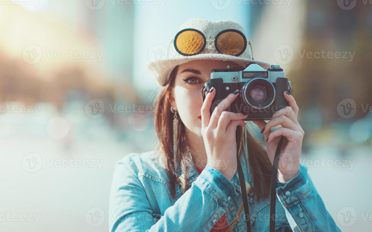 ragazza dei pantaloni a vita bassa che fa foto con la retro macchina fotografica, fuoco sulla macchina fotografica