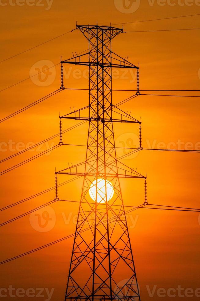 sagoma della torre ad alta tensione e il sole foto