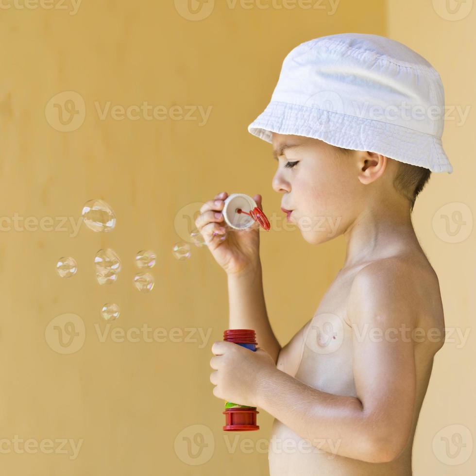 ragazzo che soffia bolle di sapone foto