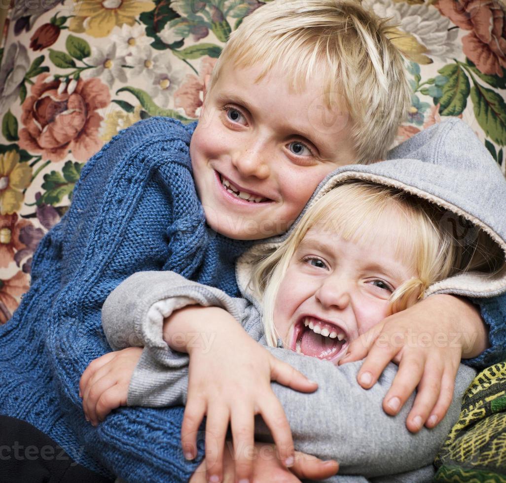 simpatici fratelli biondi si rannicchiano giocosamente foto