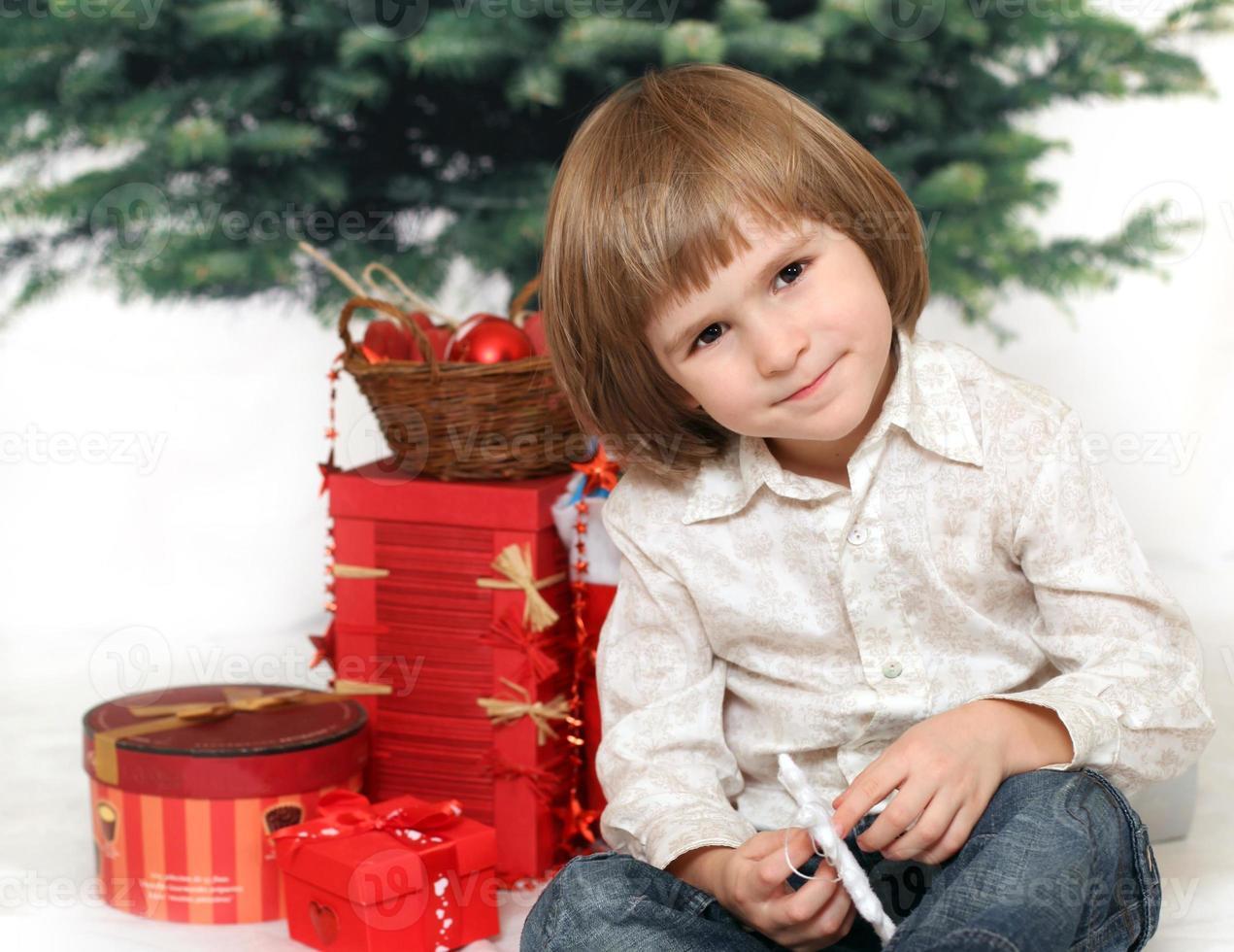 kinder con doni sotto l'albero di pelliccia foto