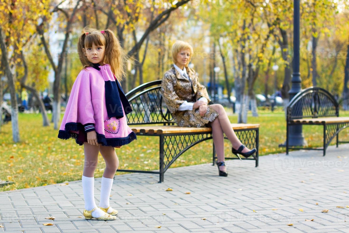 bambina graziosa nel parco di autunno foto