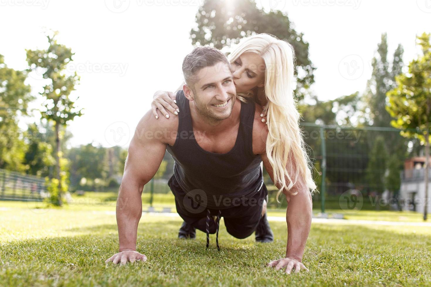 uomo adatto facendo flessioni con la donna sulla schiena foto