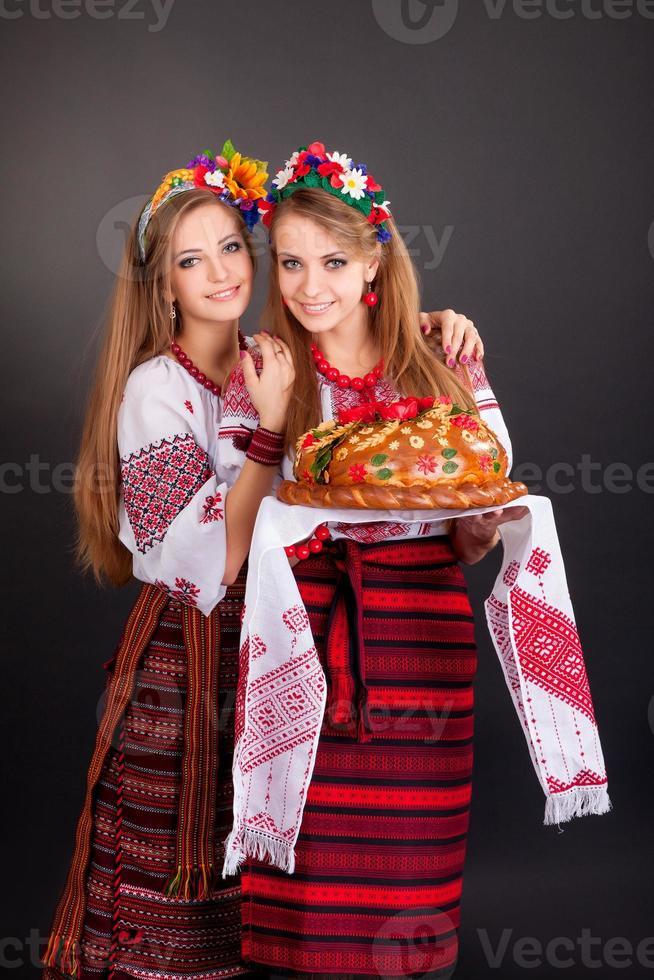 giovani donne in abiti ucraini, con ghirlanda e pagnotta rotonda foto