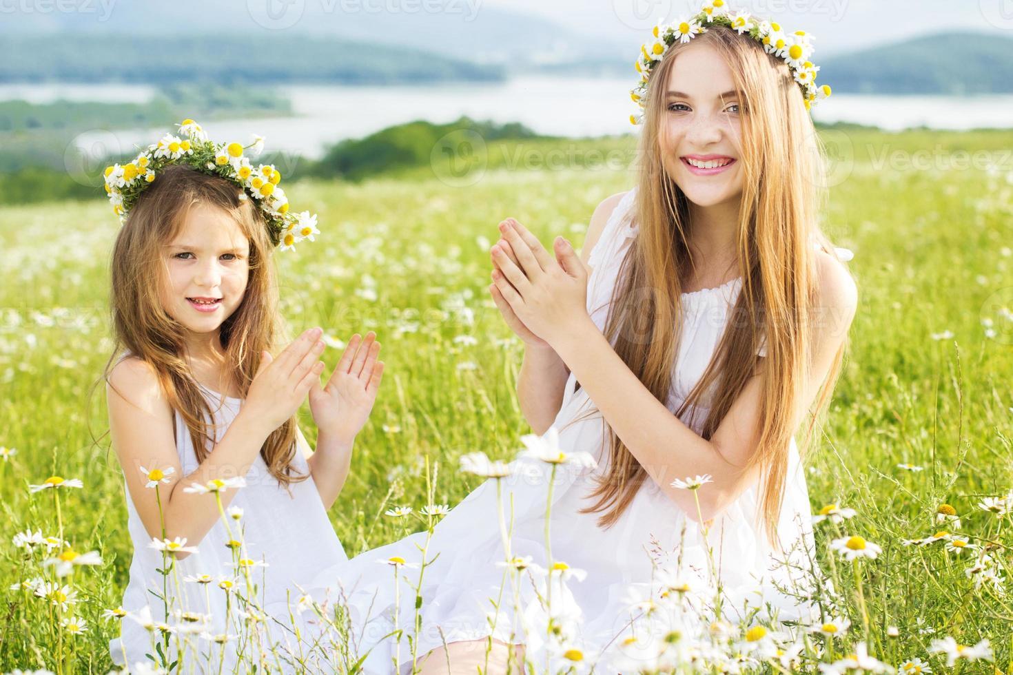 ragazze di due amici a prato di camomille foto