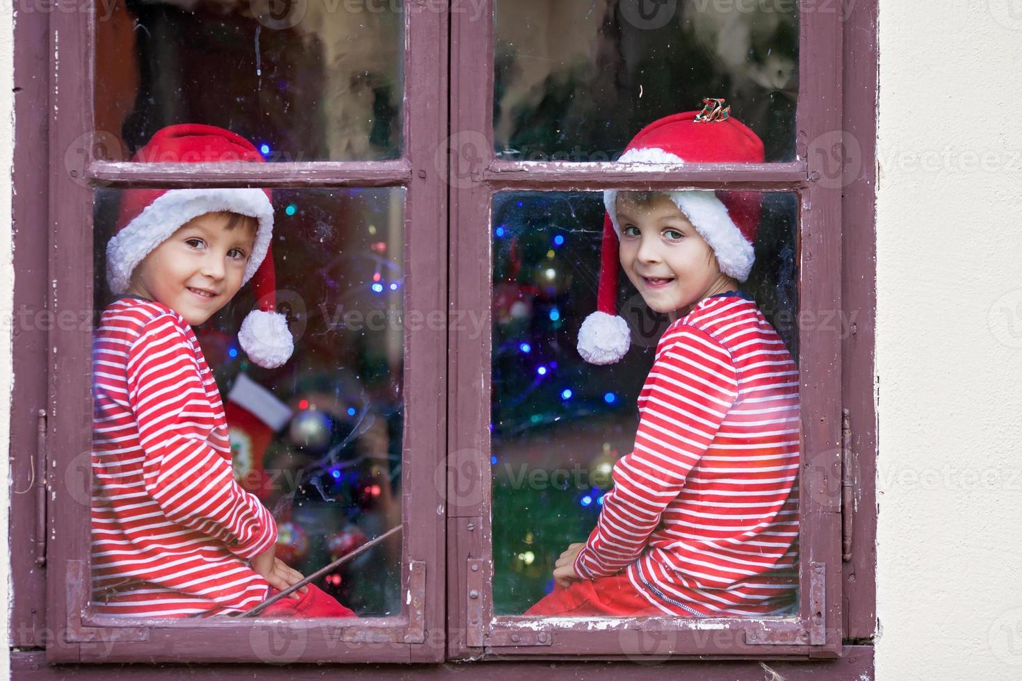 due ragazzi carini, fratelli, guardando attraverso la finestra, aspettando Babbo Natale foto