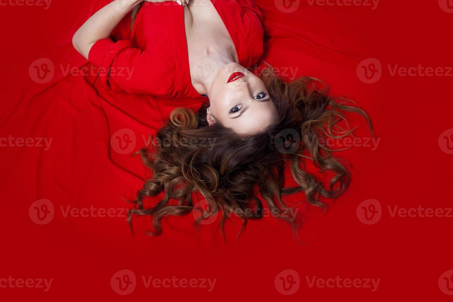 donna in abito si trova su uno sfondo rosso foto