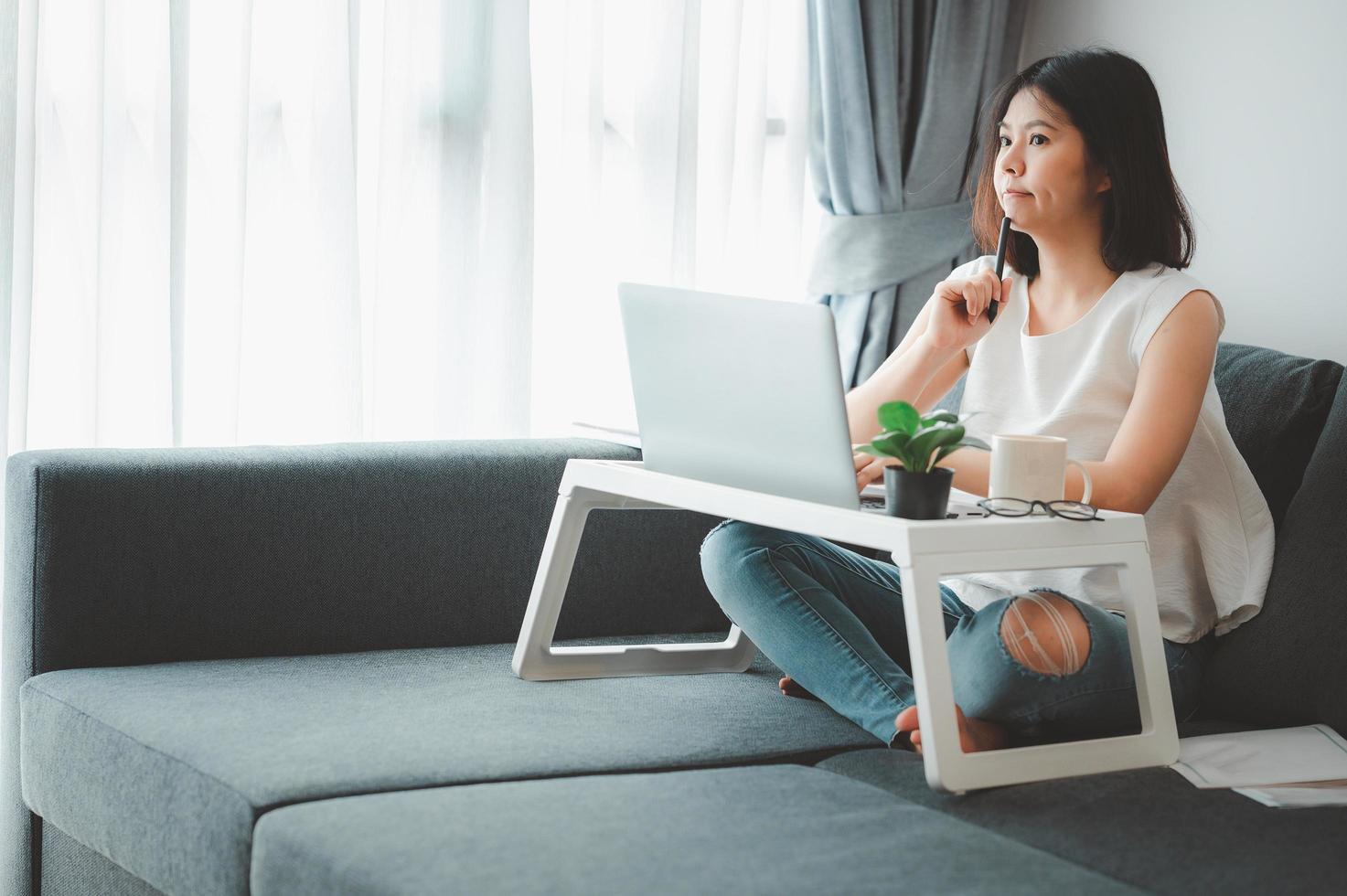 donna che lavora da casa sul divano foto