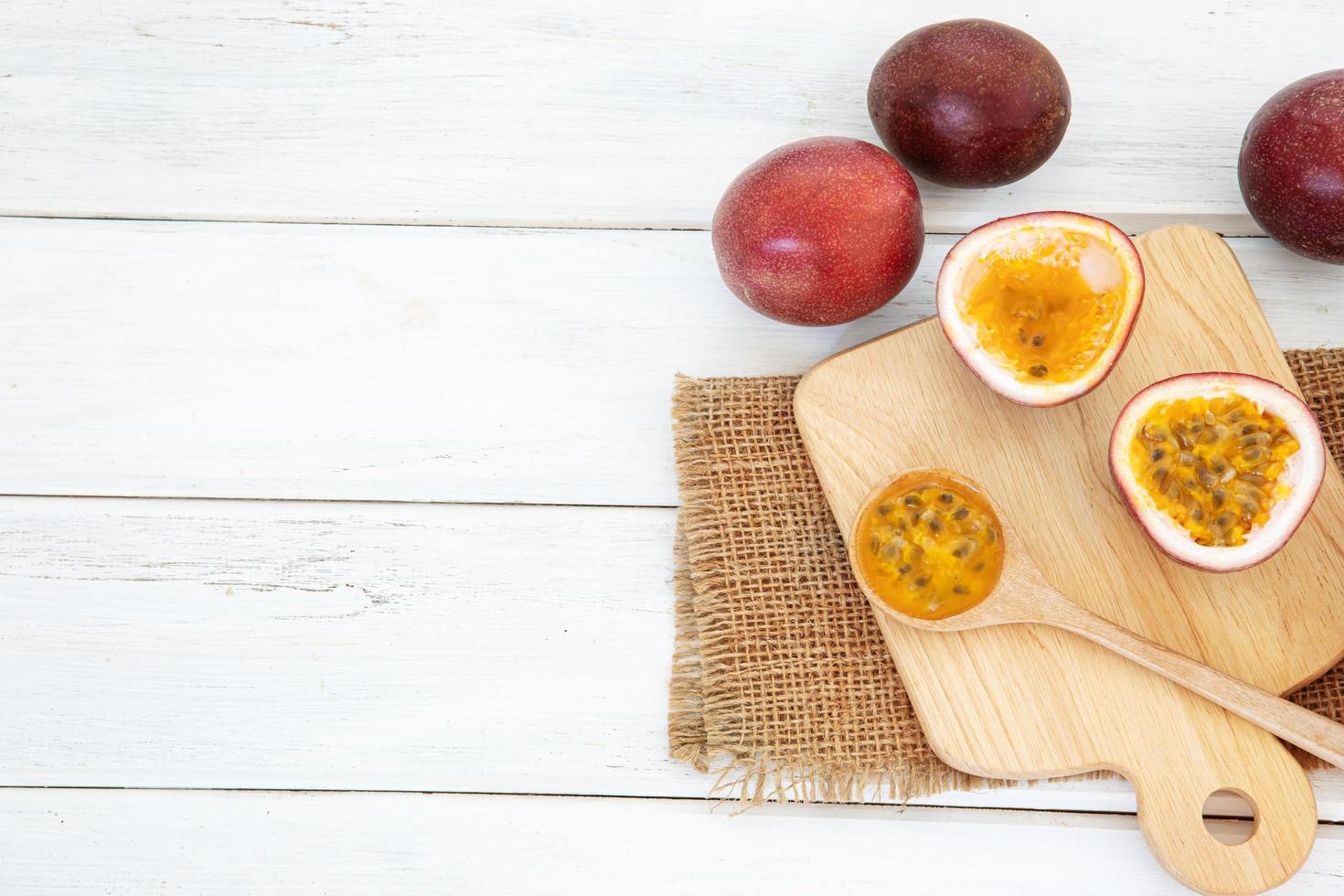 Frutti della passione freschi sul tavolo di legno bianco con tagliere foto