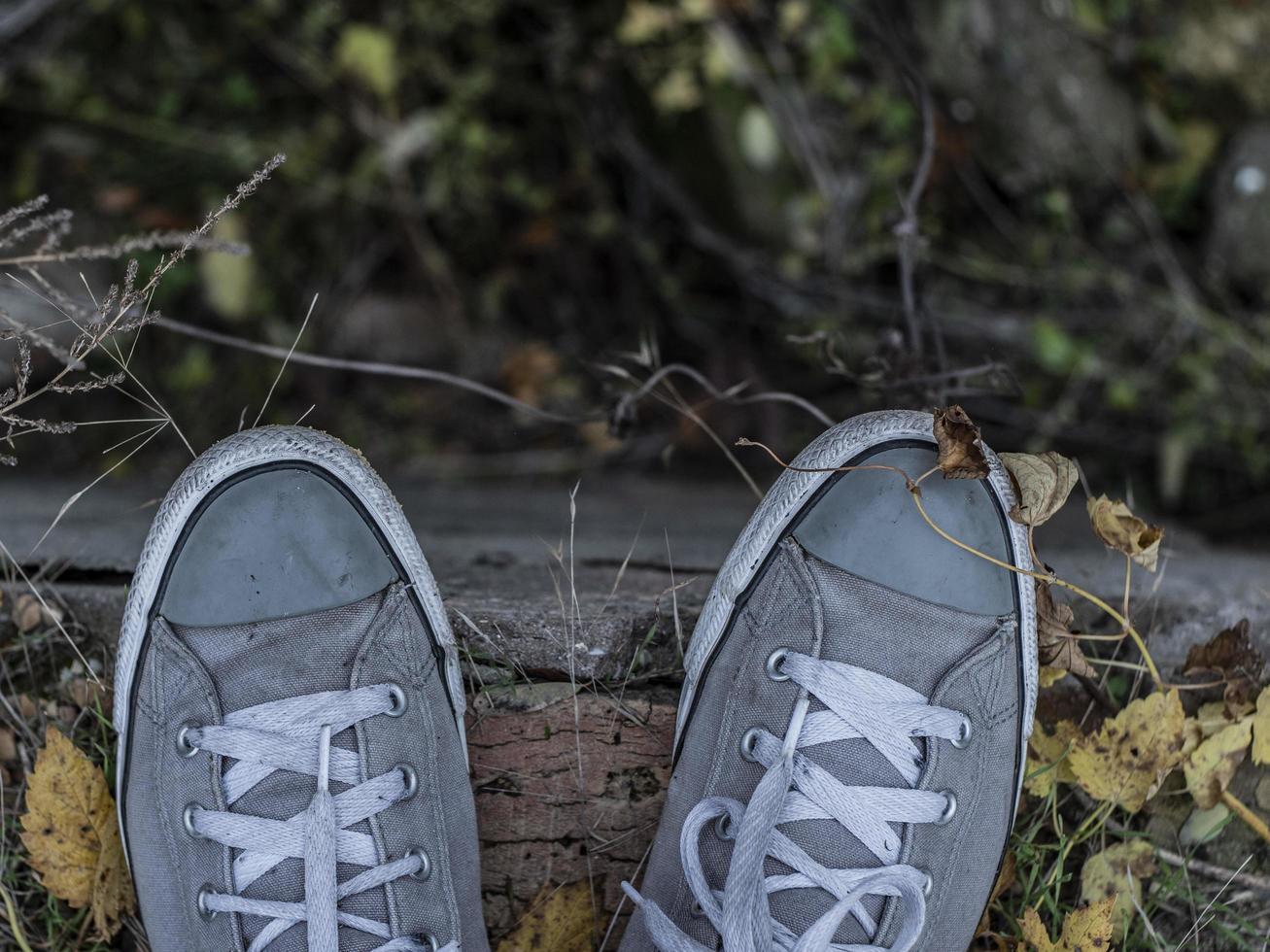 scarpe da ginnastica grigie sul visualizzatore che guardano sotto foto