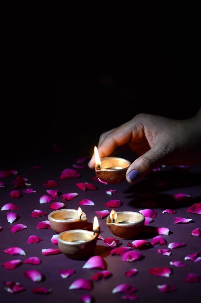 mano ponendo la candela sul letto di petali foto
