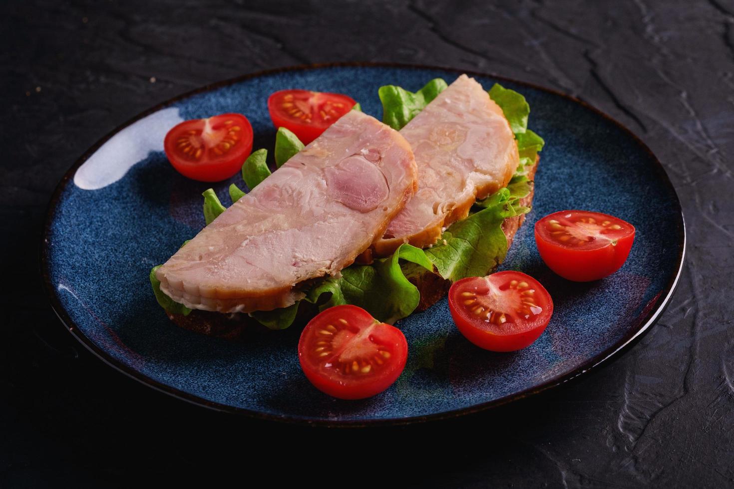 sandwich con carne di prosciutto di tacchino e pomodori laterali foto
