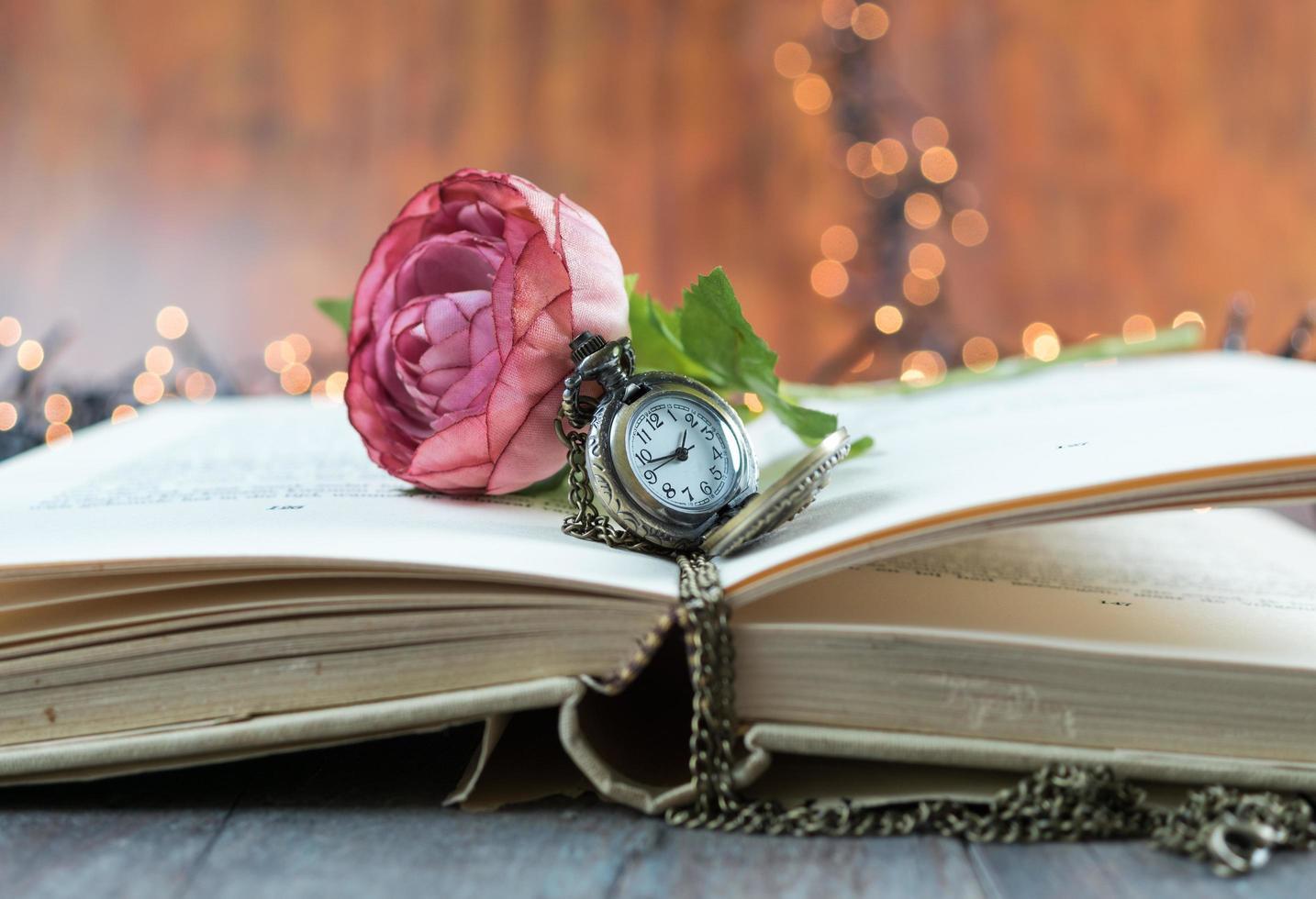 libro aperto con orologio da tasca e fiore foto
