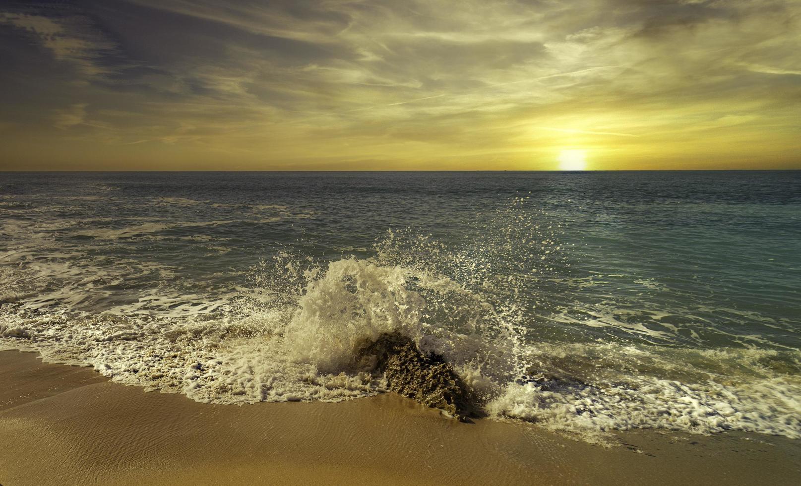 onde che spruzza sulla spiaggia al tramonto foto
