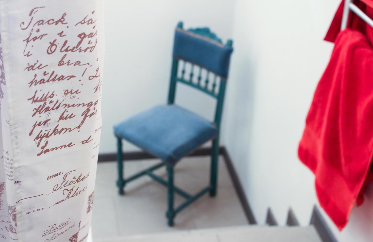parole sulla tenda accanto alla sedia blu e asciugamano rosso foto