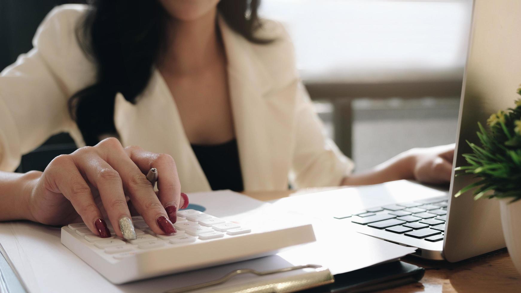 primo piano della donna di affari che per mezzo del calcolatore foto