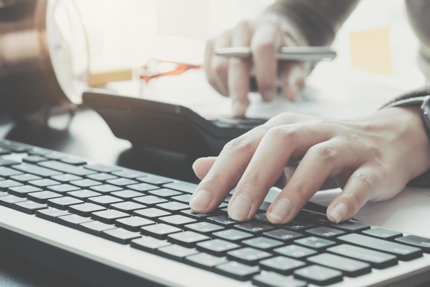 digitando professionale di affari sulla tastiera mentre si utilizza il calcolatore foto