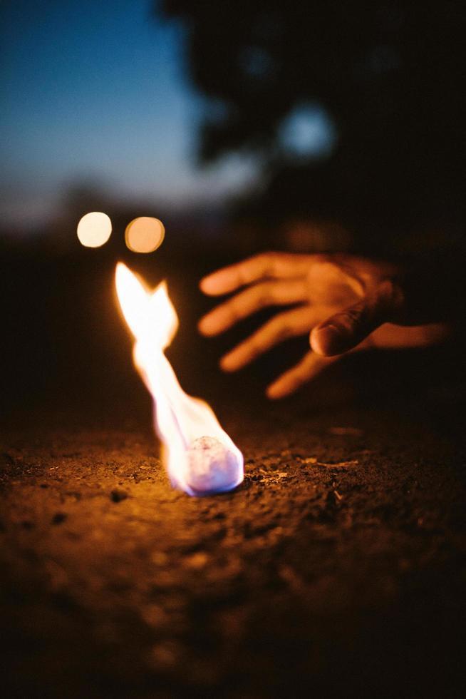 persona che raggiunge per pietra ardente foto
