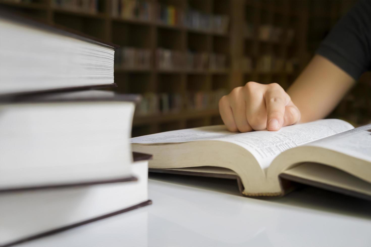 primo piano di una persona che legge in una biblioteca foto