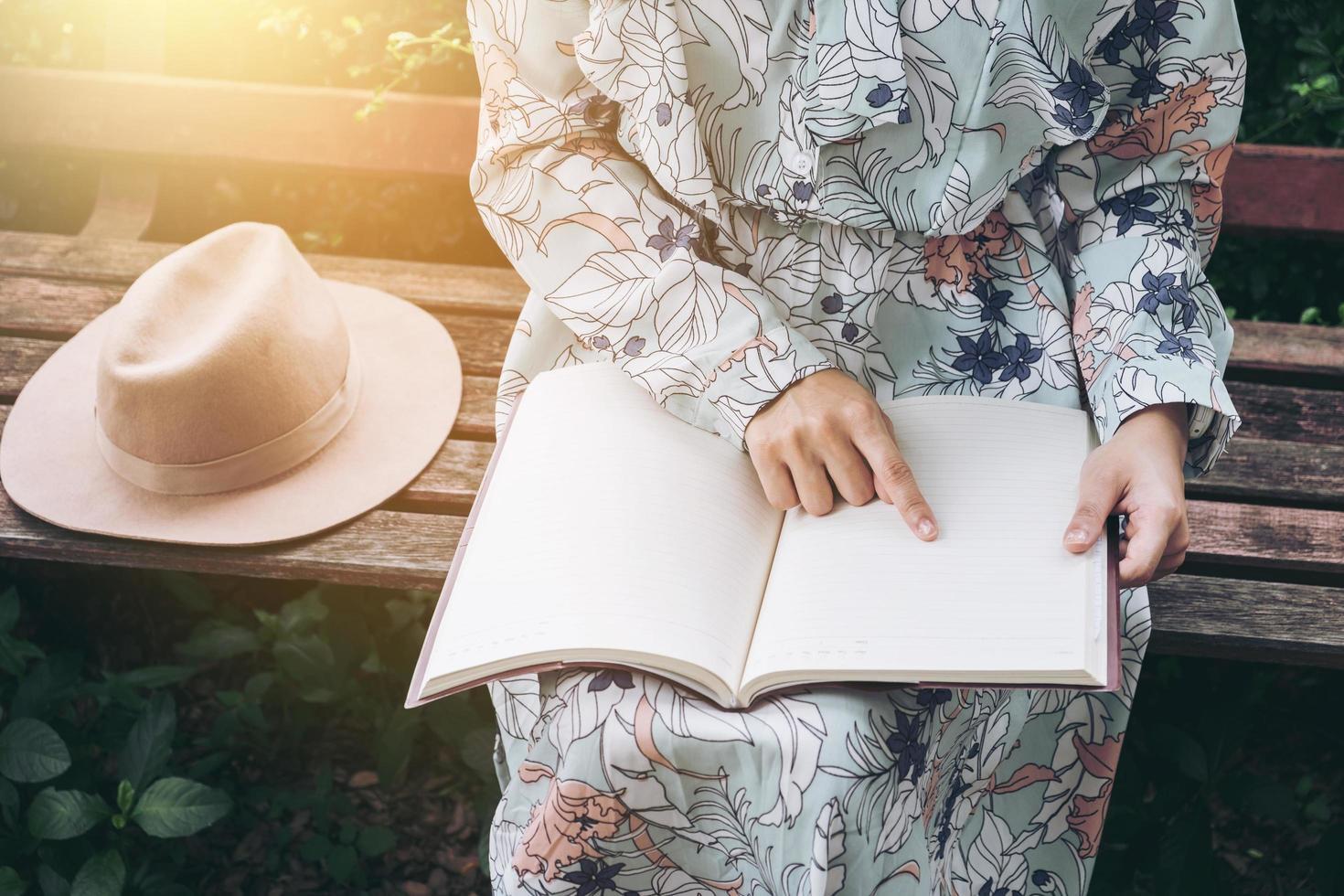 donna che punta al libro bianco al parco foto