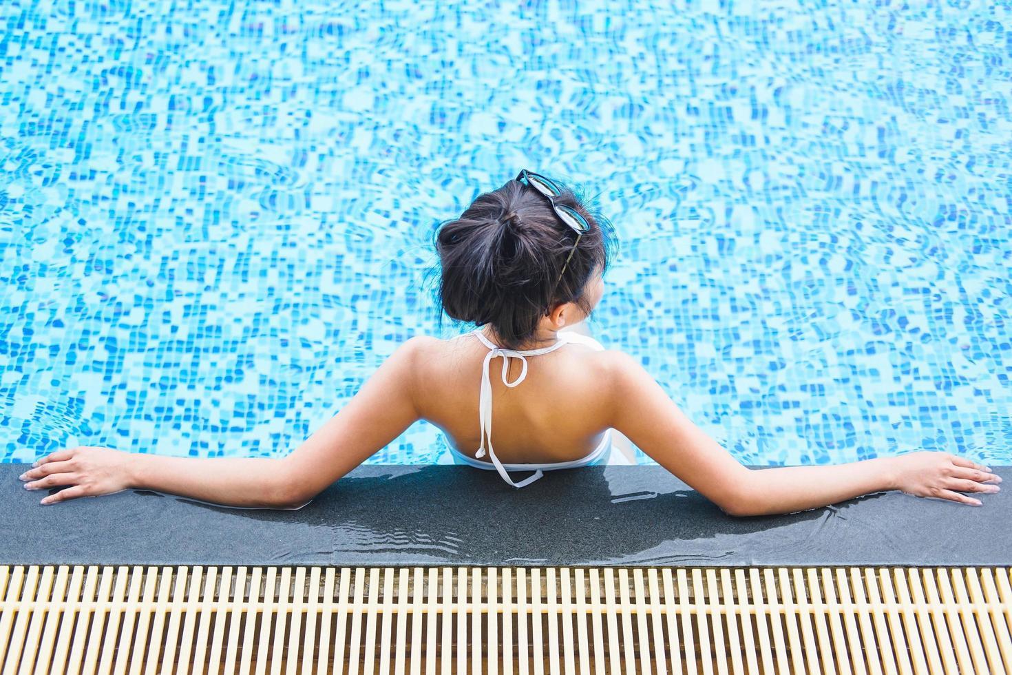 donna che si distende in piscina foto
