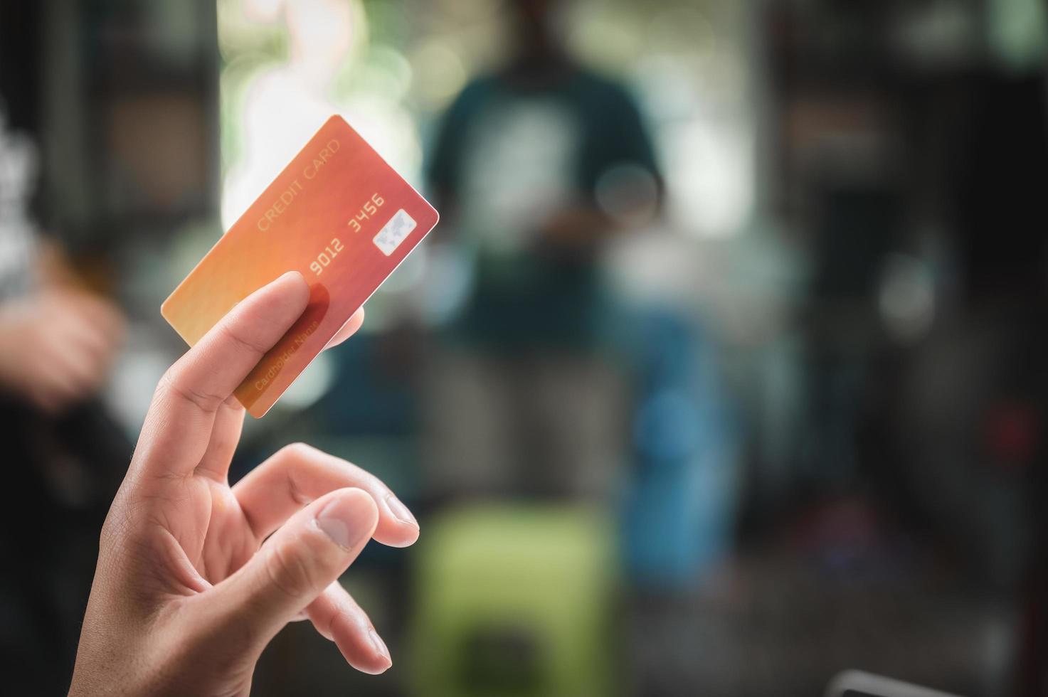primo piano della mano che tiene la carta di credito foto