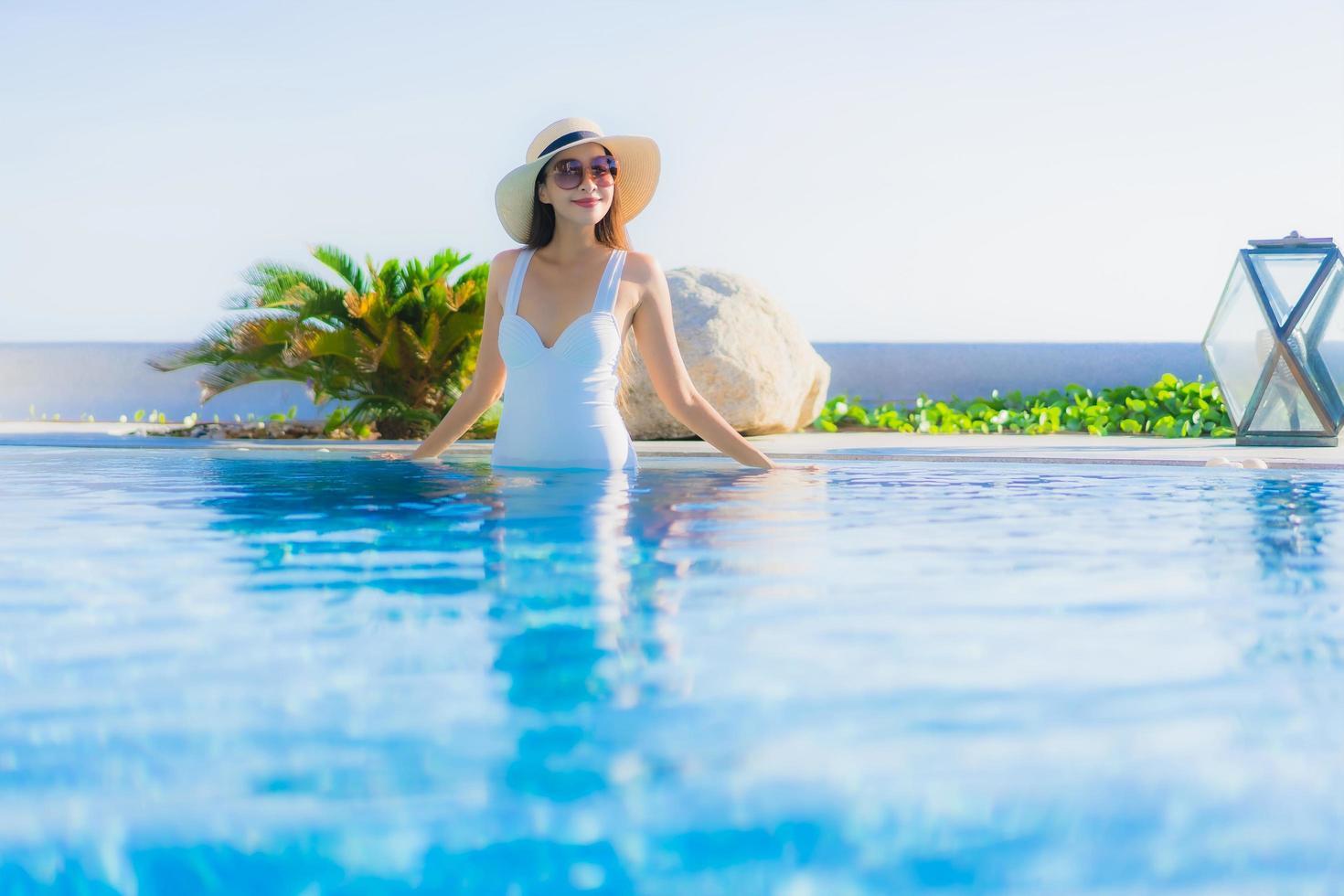donna che si distende nella piscina all'aperto foto