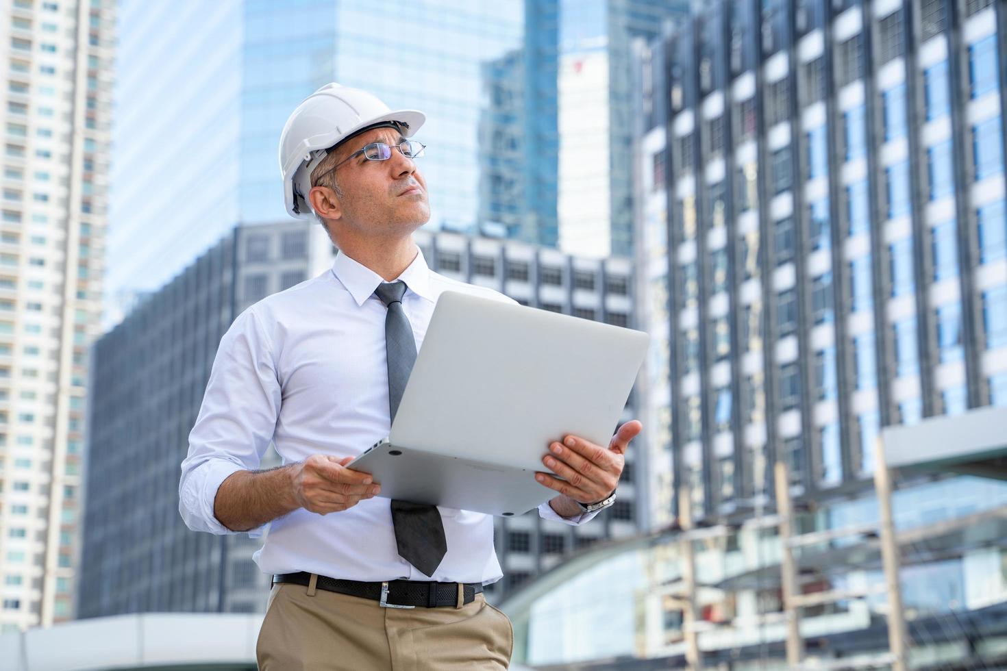 uomo d'affari che lavora al computer portatile all'esterno foto