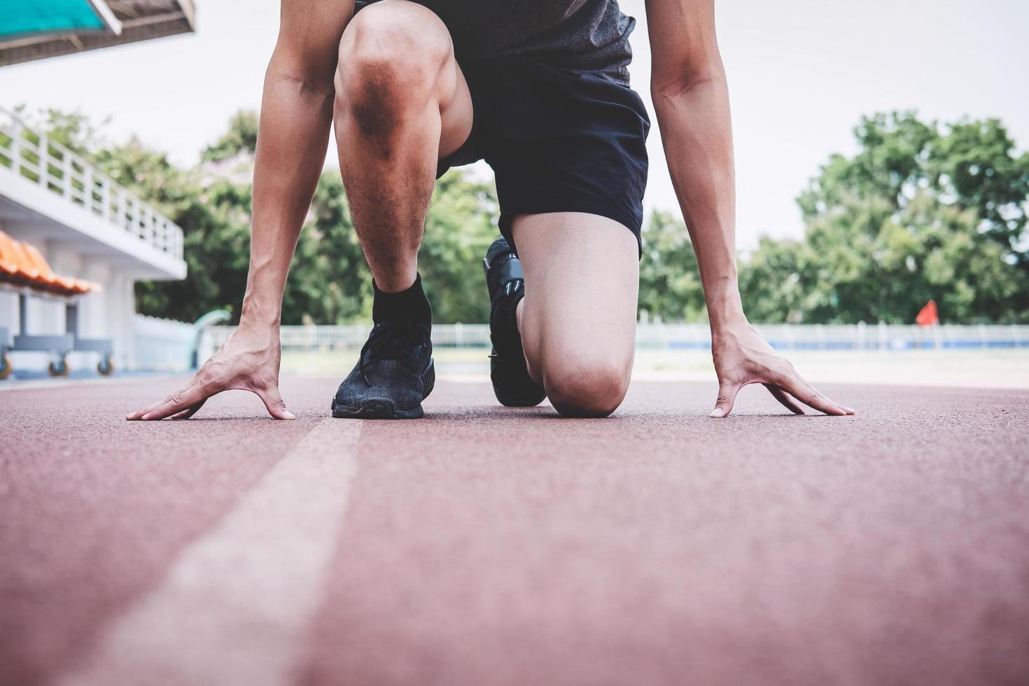 in esecuzione preparando a correre sulla pista di atletica foto