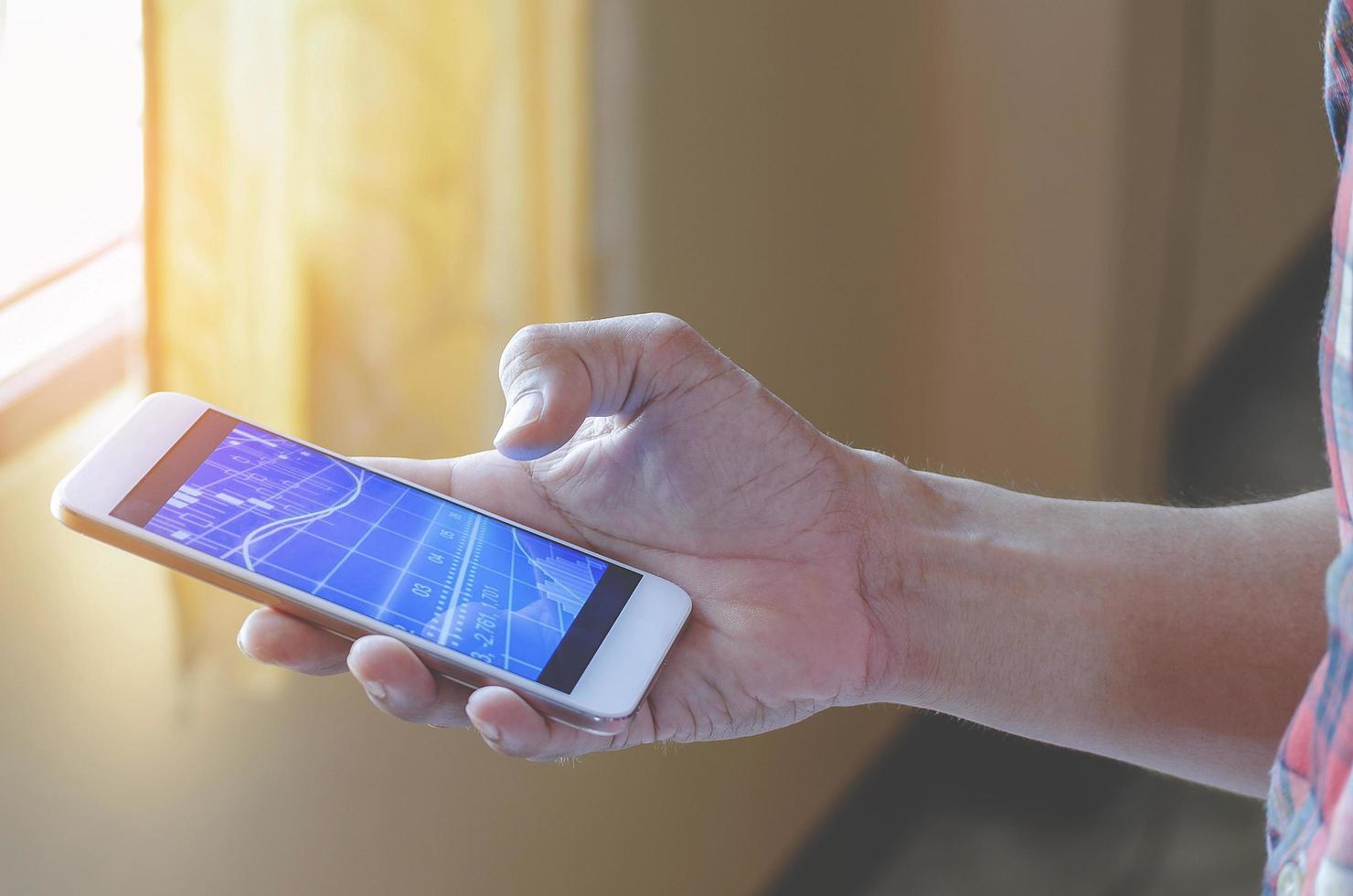 persona in possesso di smartphone in mano foto