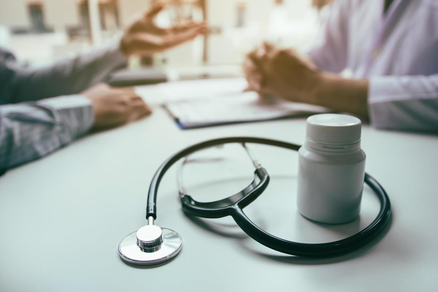 stretta di stetoscopio e bottiglia di medicina foto
