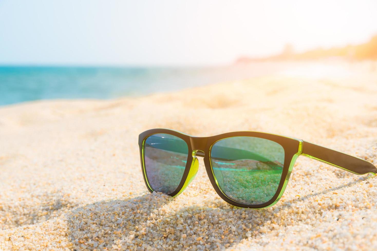 occhiali da sole sulla spiaggia foto