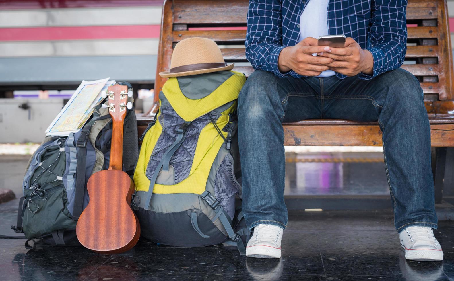primo piano del viaggiatore utilizzando smartphone alla stazione ferroviaria foto