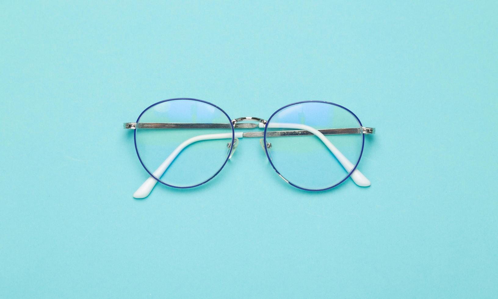 occhiali su sfondo blu foto