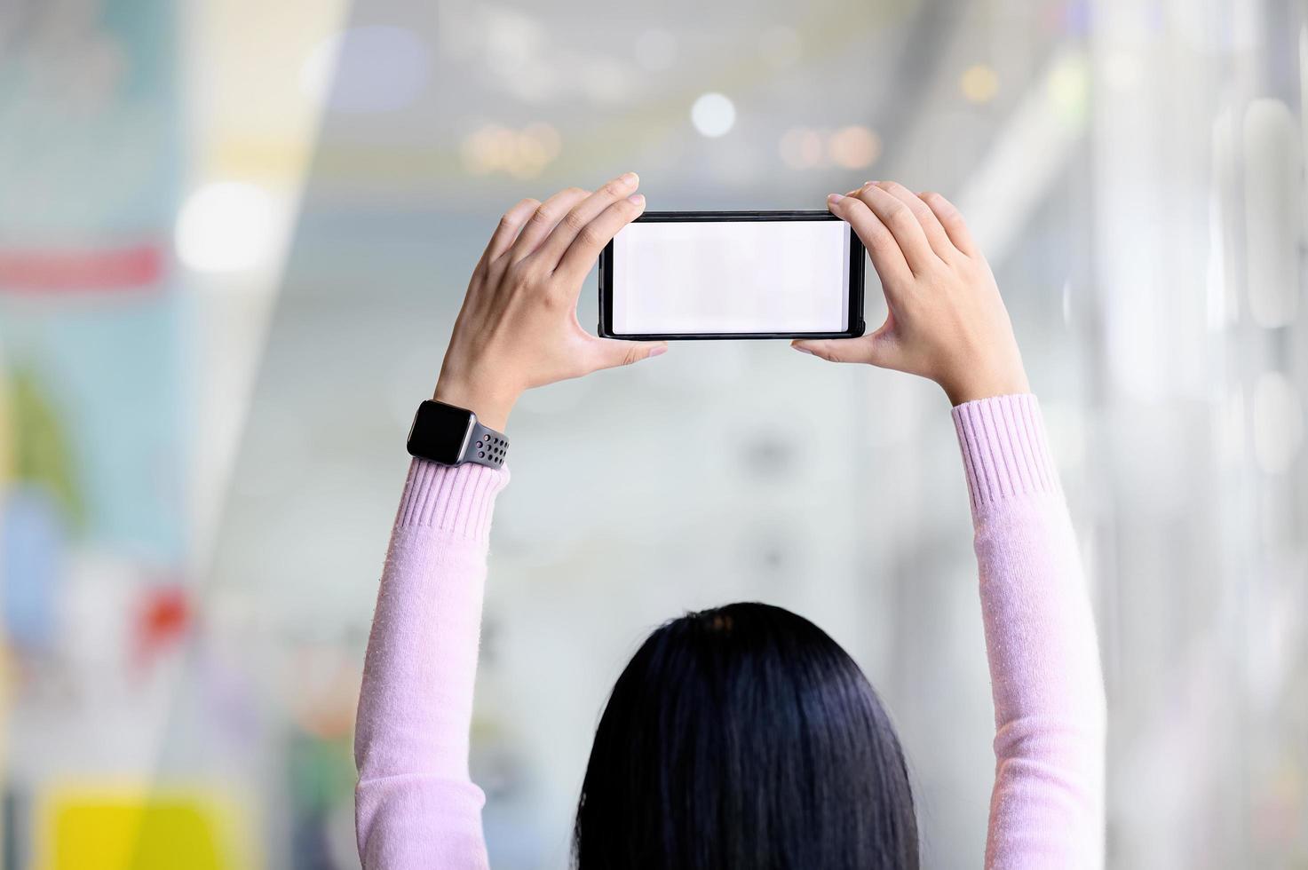 mano femminile che tiene telefono astuto foto