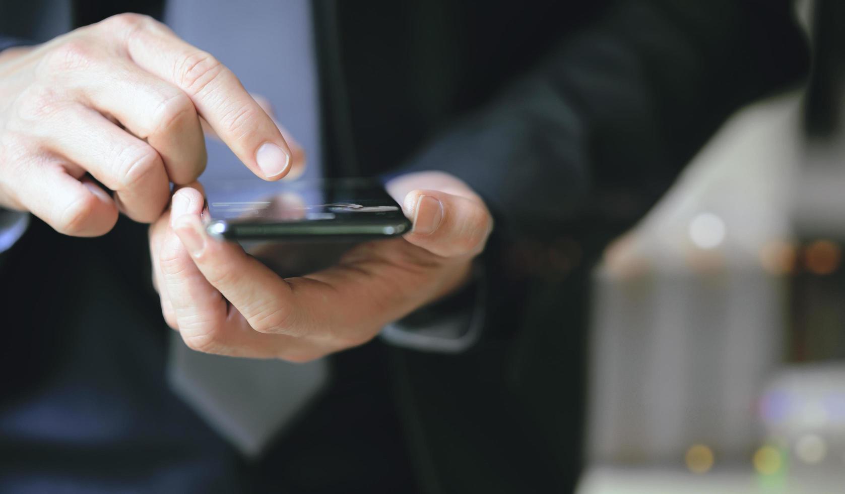 primo piano dell'uomo d'affari che per mezzo dello smartphone foto