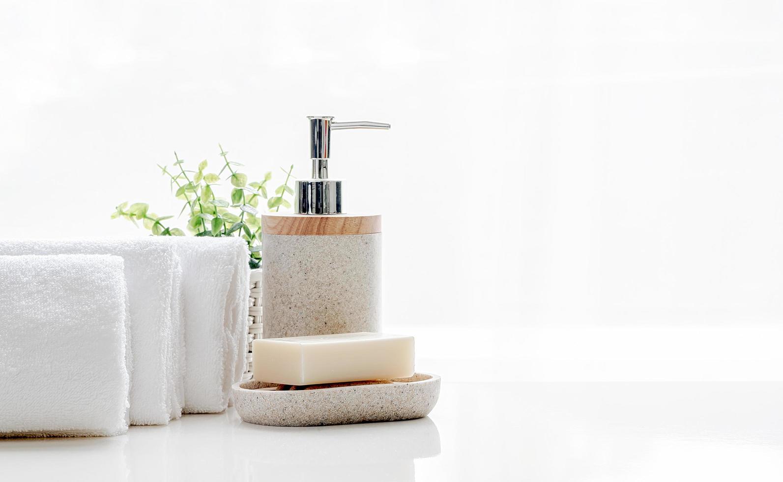 pulire asciugamani di spugna morbidi con sapone sul tavolo bianco foto
