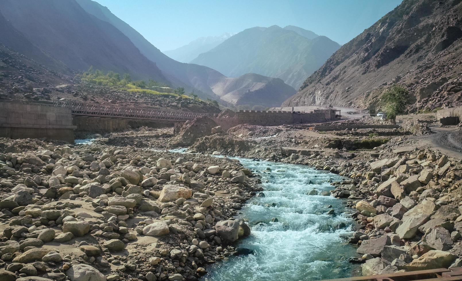 fiume che scorre lungo la catena montuosa del karakoram in estate foto